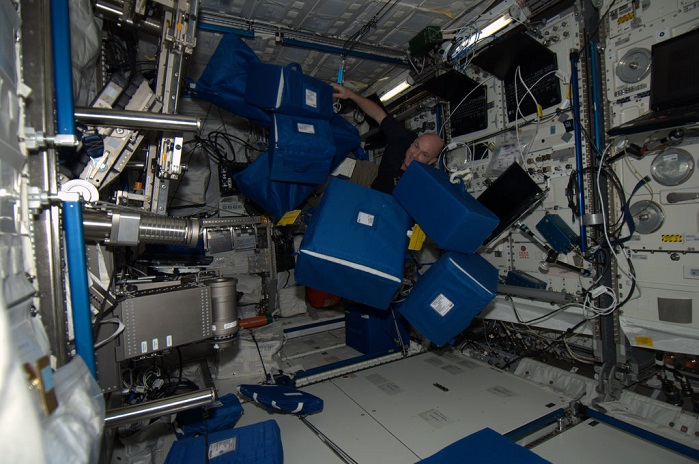 Astronaut André Kuipers with textile transportation bags at ISS. © University College Ghent