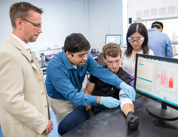 Graduate students Mengya Li and Nitin Muralidharan adjust the energy harvesting device on the arm of undergraduate Thomas Metke while Professor Cary Pint looks on. © John Russell / Vanderbilt