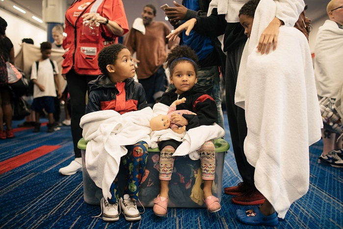 Children waiting to check in at the temporary shelter at the George R. Brown Convention Center in downtown Houston. Shown with donated Standard Textile towels. © Alyssa Schukar
