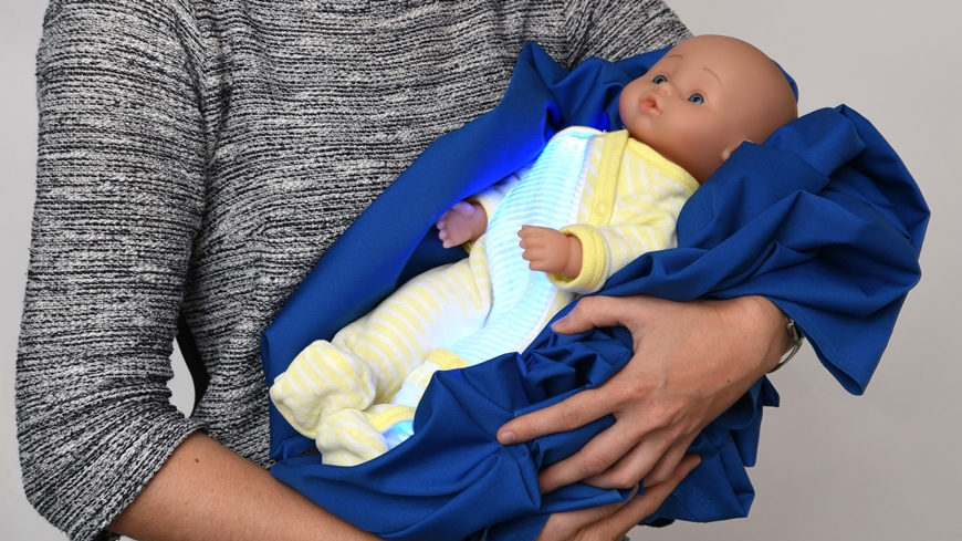 For demonstration purposes, the illuminated textile was sewn into a traditional romper suit. For future clinical applications, the pajamas will only emit their blue light inward, directly onto the child's skin. © Empa
