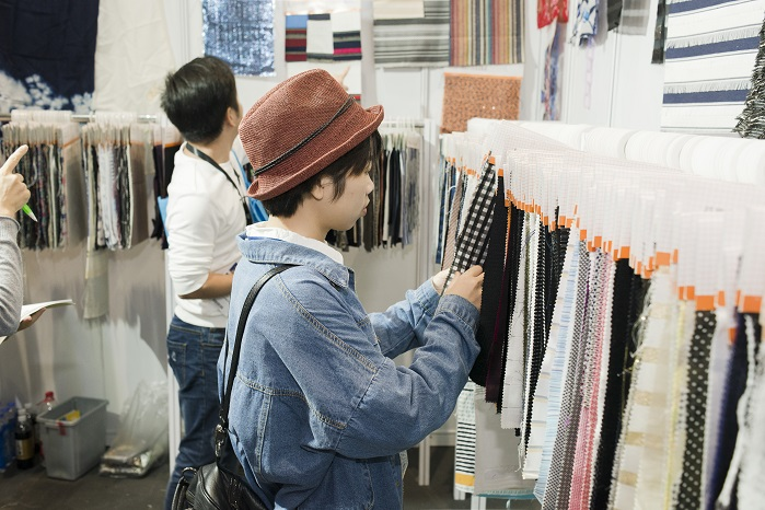 Buyer with products. © Messe Frankfurt / Intertextile Shanghai Apparel Fabrics
