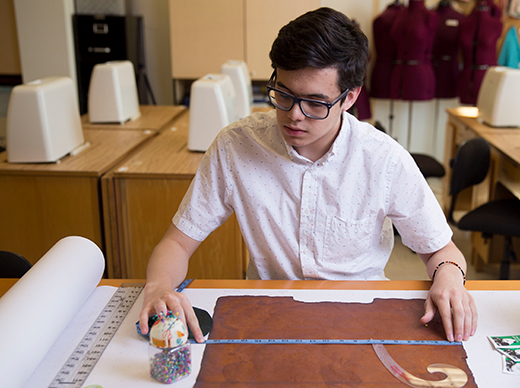 Senior fashion design student Luis Quijano measures and cuts a material he grew himself using a mixture of ordinary household ingredients. © Jessie Rogers