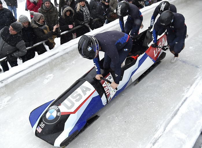 A four-man bobsled team powers the USA sled off the block at the start before loading for a race run in the Igls, Austria World Cup in December 2017. © Solvay