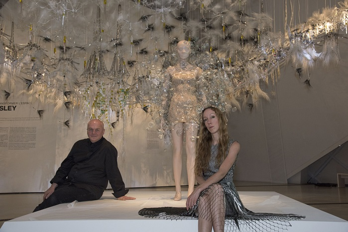 Iris van Herpen and Phillip Beesley with the Dome dress at the ROM seen against a backdrop of Beesley's interactive Aegis canopy that uses a curiosity algorithm to constantly change and search for new patterns of behaviour. © ROM