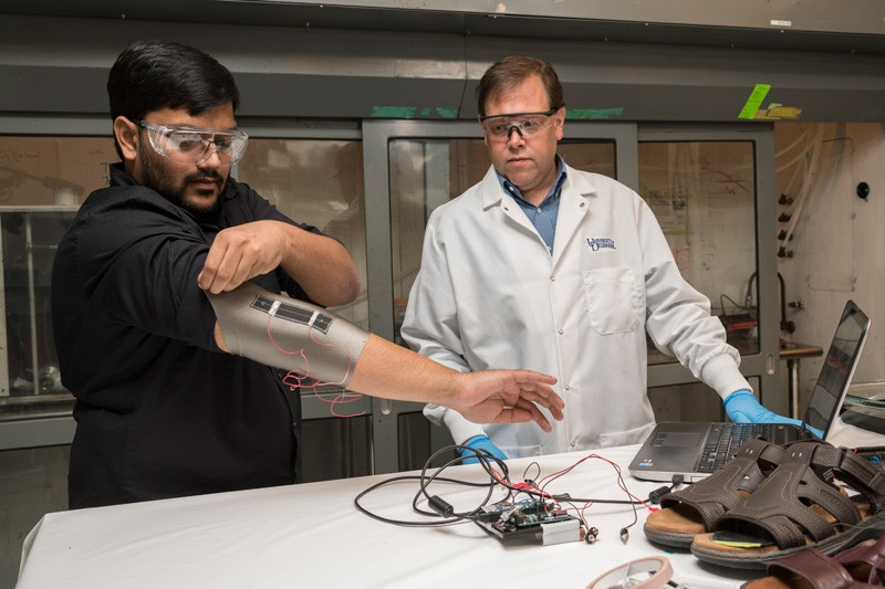 Sagar Doshi (left) and Erik Thostenson test an elbow sleeve outfitted with one of their novel sensors. © University of Delaware